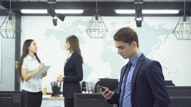 ビジネスコンセプト。フォーマルな服装の青年実業家は、オフィスでの仕事について話し合っている2人の若い女性従業員の背景にスマートフォンを探します