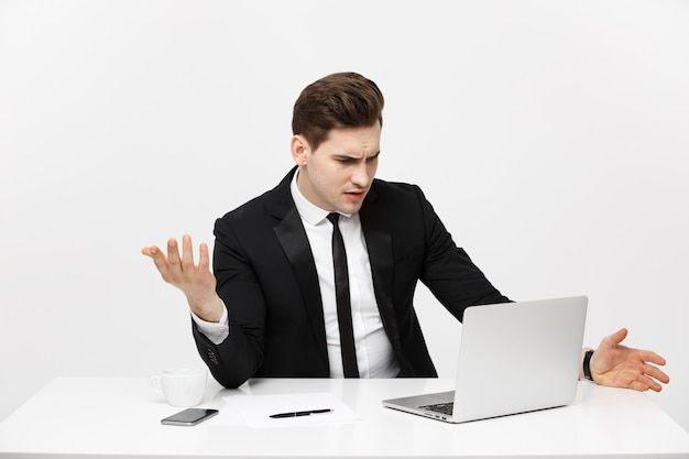 Business concept young businessman working in bright office sitting at desk using laptop with seriou...