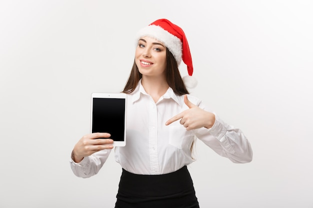 Business concept - young caucasian business woman in christmas theme showing and pointing to digital tablet.