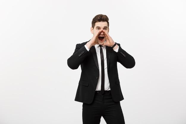 Concetto di affari: giovane uomo bello di affari che grida e isolato su bianco.