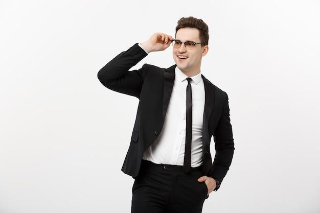Concetto di affari: giovane uomo d'affari bello con gli occhiali tenendo la mano in tasca isolata su sfondo bianco.