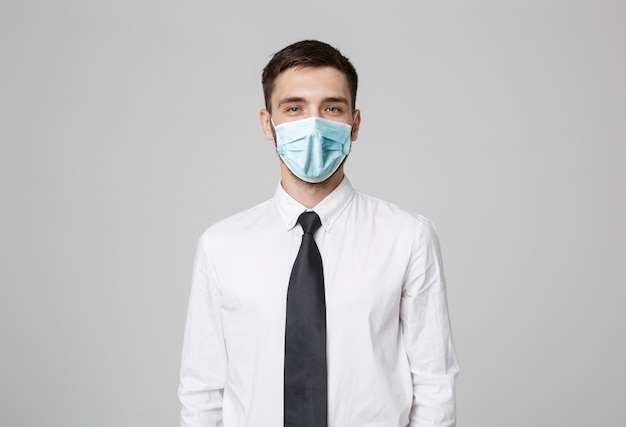 Business concept - young successful businessman in face mask posing over dark wall. copy space.