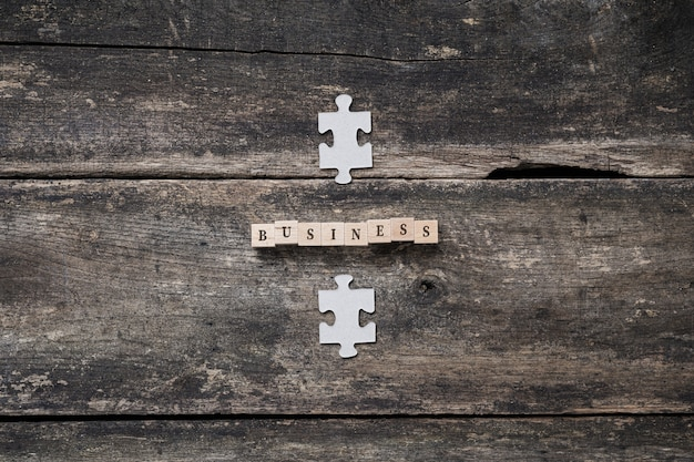 Business conceptual image - word business spelled on wooden blocks with puzzle pieces on top and below the sign