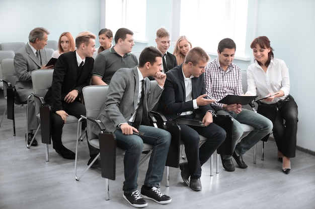 ビジネス会議。会議ホールの椅子に座っている正装のビジネスマンのグループ