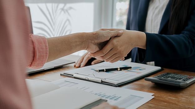 ビジネスの自信を持って握手と成功のコンセプトを議論した後のビジネス人々