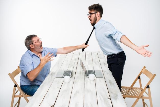 Conflitto di affari. i due uomini esprimono negatività mentre un uomo afferra la cravatta del suo avversario