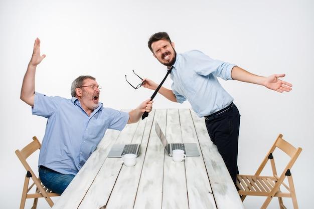 Conflitto commerciale. i due uomini esprimono negatività mentre un uomo afferra la cravatta del suo avversario