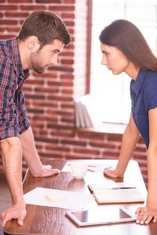 비즈니스 대결입니다. 사무실 테이블에 기대어 얼굴을 맞대고 서 있는 화난 남자와 여자의 측면 이미지
