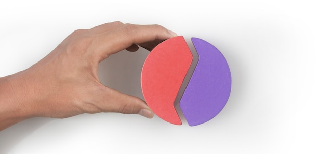 Business connecting piece of multi colored pie wood chart  in hand