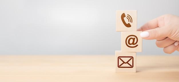 ビジネス接続は私達に連絡し、コールセンターのカスタマーサービスの概念、アイコンの携帯電話、電子メールの封筒、電話および電子メールアドレス。お問い合わせシンボルと木製ブロックを押す手