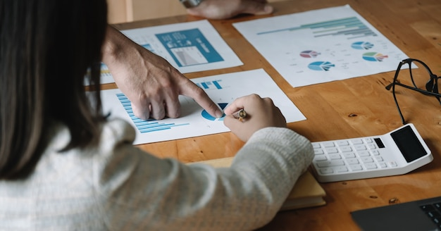 Business consultant describes a marketing plan to set business strategies for women business owners with using calculator. business planning and business researching concept.