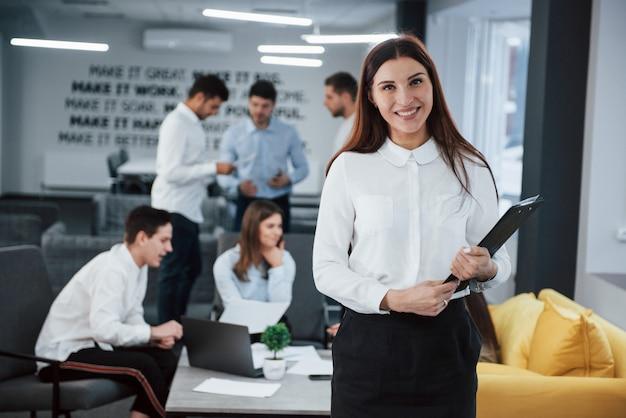 ビジネスコンサルタントは仕事の準備ができています。バックグラウンドで従業員とオフィスに立っている若い女の子の肖像画