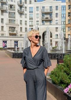 ビジネス、消費主義、そして人々の概念-現代の家を背景にサングラスをかけた年配の女性。大都市の不動産エージェント。