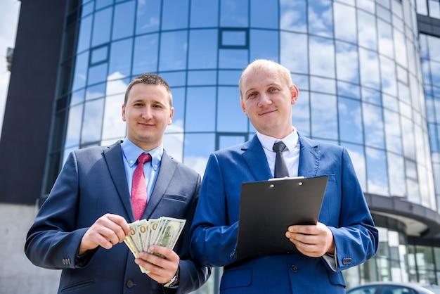 Деловой контракт на открытом воздухе, партнеры с долларовыми банкнотами