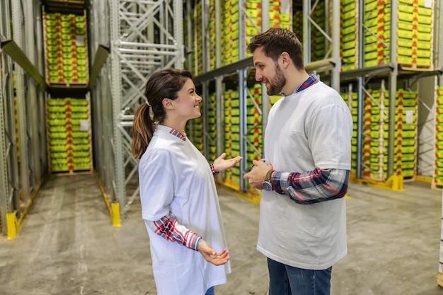 Деловая беседа и отчетность. мужчина и женщина стоят посреди склада перед полками с коробками и обсуждают текущие проекты. приятный разговор и женщина улыбается, работа