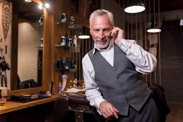 비즈니스 대화. 안락의 자에 기대어 이발소에서 휴대 전화에 얘기하는 동안 웃 고 잘 생긴 수염 된 수석 남자.