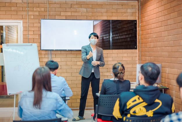 Business cooperation : young asian male coach or speaker make flip chart presentation to diverse businesspeople at meeting in office. male tutor or trainer present project to diverse colleagues.