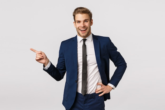 Business, corporate and entrepreneur concept. handsome cheerful blond bearded businessman in suit, talking to coworkers, smiling happy and relieved, finish office meeting, pointing left