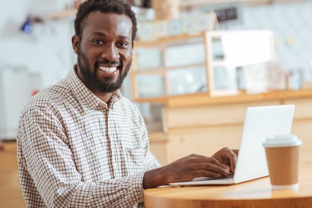 Деловая переписка. очаровательный улыбающийся мужчина сидит за столом в кафе и печатает электронное письмо, улыбаясь в камеру