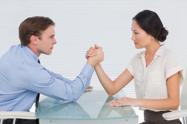 Business couple arm wrestling at desk