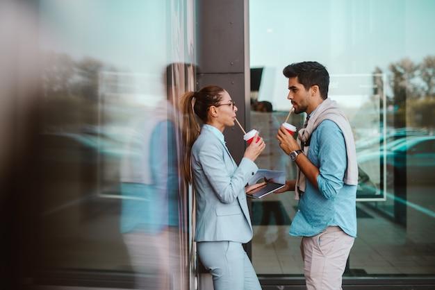 外でコーヒーブレークでビジネスカップル。カジュアルなビジネス。