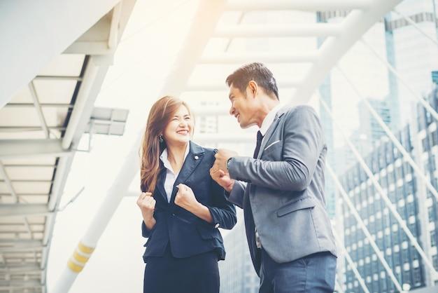 ビジネスカップルは、野外ではいをしています。チームワークのコンセプト