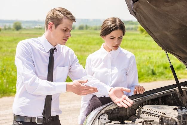 Business couple having argument by broken car.