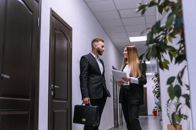 現代のオフィスの廊下に立って話しているビジネスカップルの肖像画の若い男性と女性