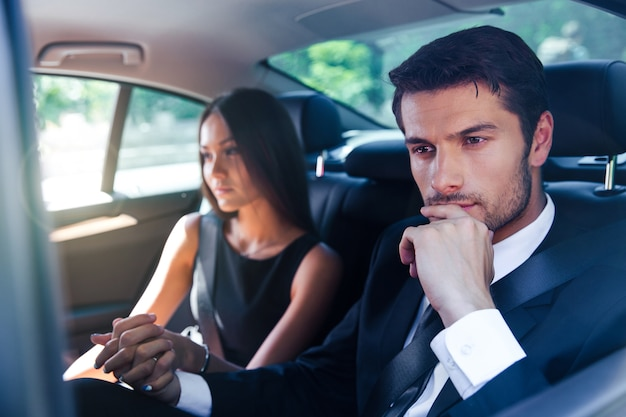 Business couple riding in car together