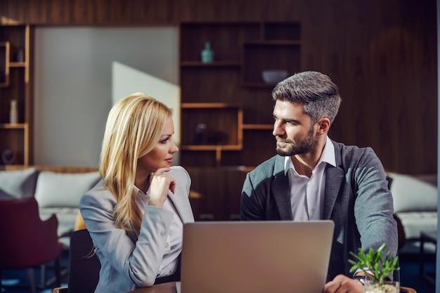 Деловая пара, сидя в кафе и разговаривая по делу. на столе лежит ноутбук. деловая встреча, технологии, сотрудничество