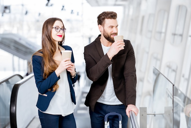 Business couple waiting with coffee to go at the airport. business travel concept