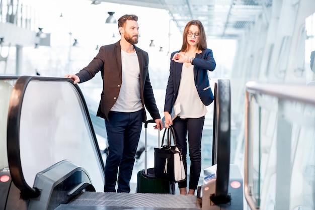 空港のエスカレーターで起き上がる手荷物チェック時間を持つビジネスカップル