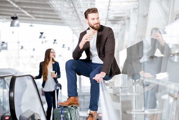Business couple with coffee to go at the airport. business travel concept