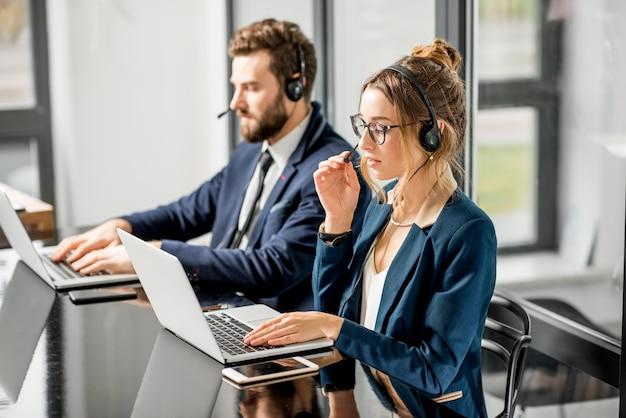 オフィスに座っているヘッドセットとラップトップでライン会議を持っているスーツに身を包んだビジネスの同僚