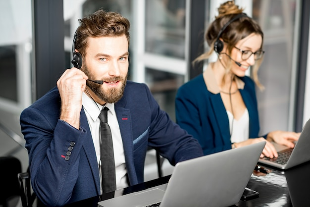Business coworkers dressed in suits having oline conference with headset and laptop sitting at the office