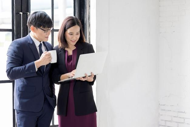Деловые коллеги с ноутбуком говорят о работе в офисе