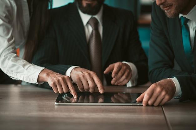 Деловой коворкинг. творческие бизнесмены, касаясь пальцами цифрового планшета, вместе работают над новым проектом. крупным планом выстрел из человеческих рук.