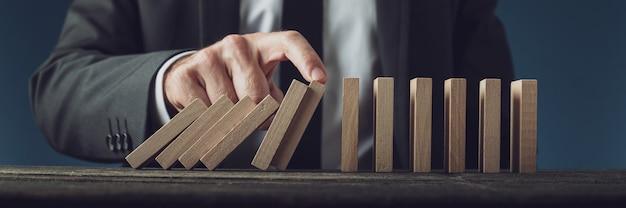 ドミノの落下と崩壊を阻止するビジネス危機管理者。青い背景の上。