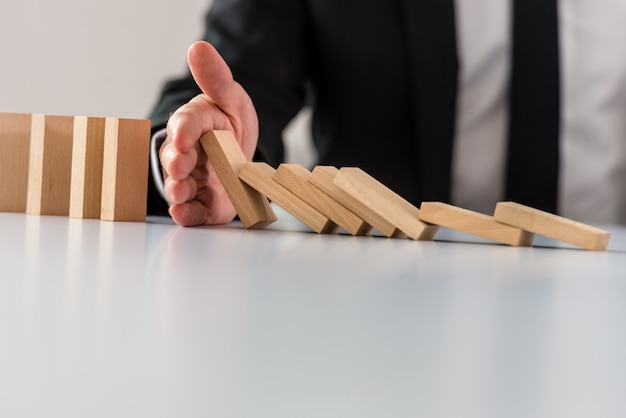 Business crisis solution concept with business manager intervening to stop collapsing dominos