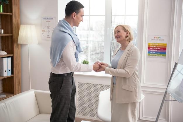 商売上の取引。立っている間挨拶するプロの2人の同僚