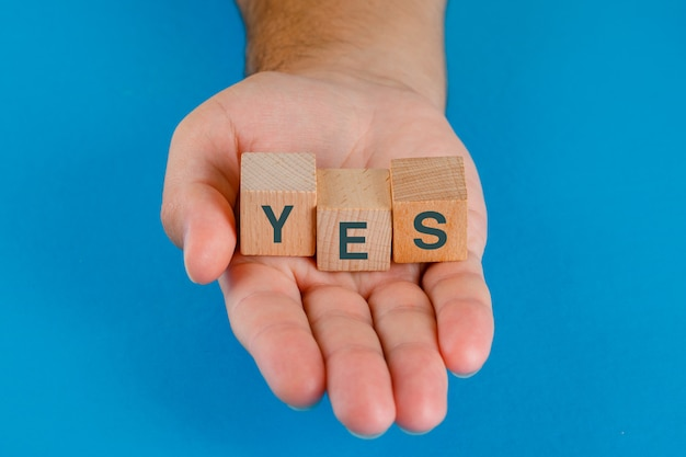 Business decision concept on blue table high angle view. hand holding wooden cubes with word yes.
