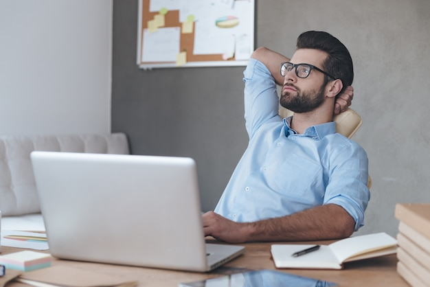 Business decision every day. pensive young handsome man wearing glasses keeping hand behind his head