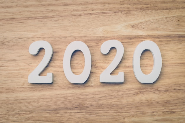 Business and design concept - wooden number 2020 for happy new year text on wood table.