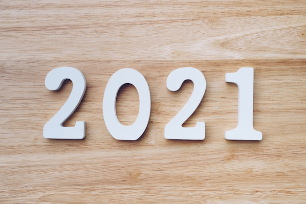 Business and design concept - wooden number 2021 for happy new year text on wood table.