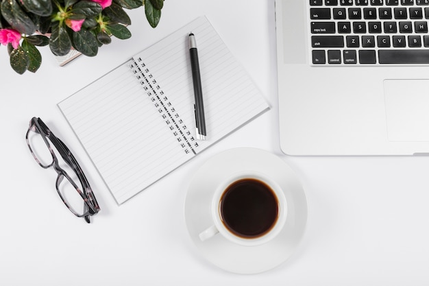 Business desk arrangement with empty notebook