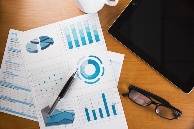 デジタルタブレット、コーヒー、眼鏡、ビジネスグラフを備えたビジネスデスク