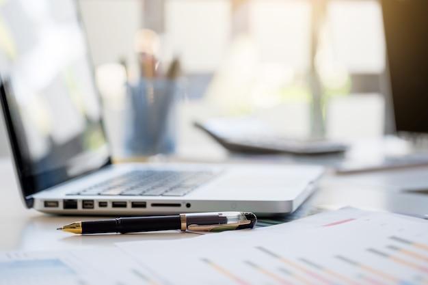 Tavolo da lavoro con una tastiera, diagramma grafico di report, penna e tavoletta sul tavolo bianco