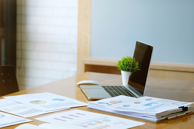 Business desk with a laptop, report graph chart, pen and document paper on wood table.