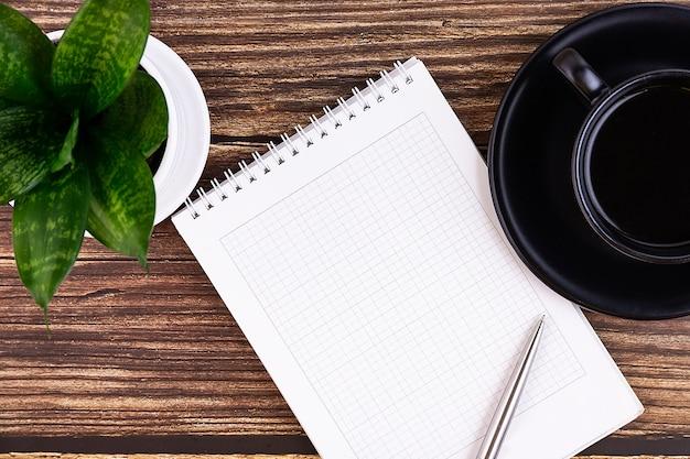 ノート、ペン、花、木製のメガネとビジネスデスク。