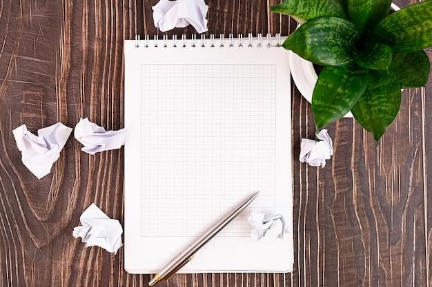 ノート、ペン、花、木の上にしわくちゃの紙が付いているビジネスデスク。